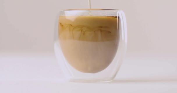 Vylévání mléka v šálku s kávou na bílém pozadí