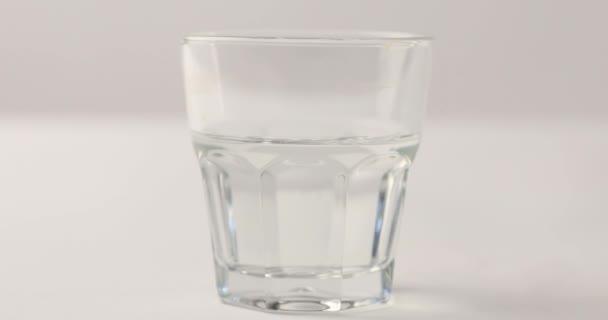 Mano che pulisce sciroppo di tabella dopo laggiunta di rosso in vetro con acqua limpida su priorità bassa bianca