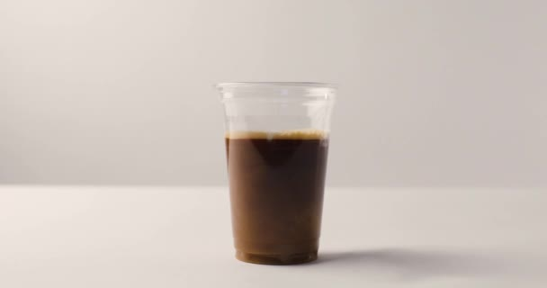 Man filling plastic cup of coffee with milk and lifting cup on white background with reverse footage