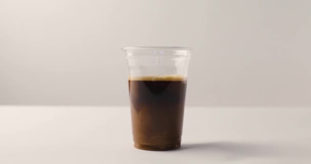 Adding milk to coffee in plastic cup on white background with reverse footage