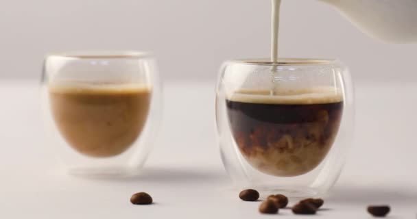 Vylévání mléka v jednom ze dvou šálků kávy na bílém pozadí s kávová zrna s reverzní záznam