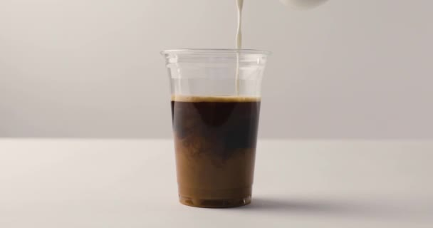 Pouring milk in plastic cup with coffee on white background with reverse footage