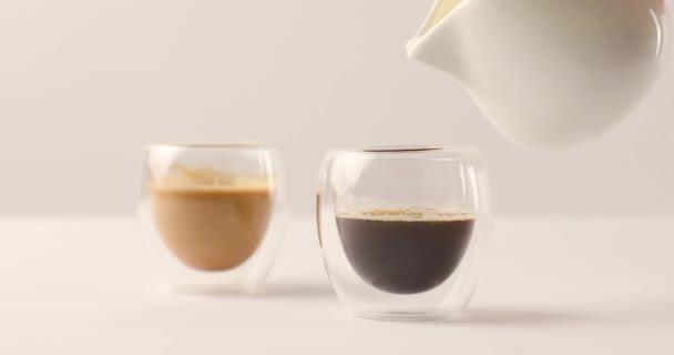 Vylévání mléka v jednom ze dvou šálků kávy na bílém pozadí
