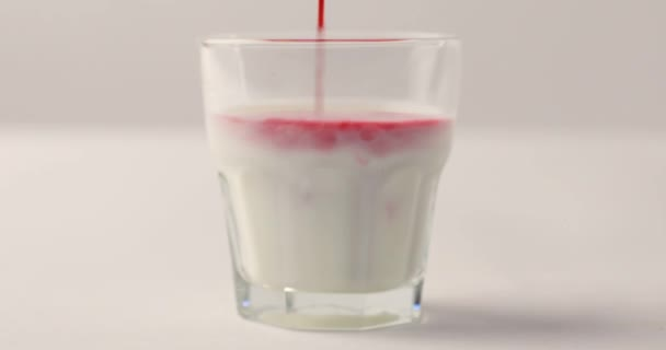 Pouring red syrup in glass with milk on white background