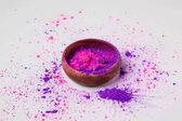 purple and pink holi powder in bowl isolated on white