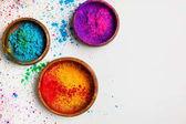 pohled shora barevné tradiční holi prášku v miskách izolované na bílém