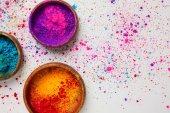 pohled shora barevné holi prášku v miskách izolovaných na bílém, tradiční hinduistická jarní festival