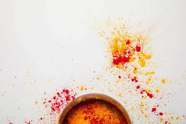 top view of orange and red holi paint in bowl isolated on white