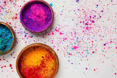 top view of colorful holi powder in bowls isolated on white, traditional Hindu spring festival