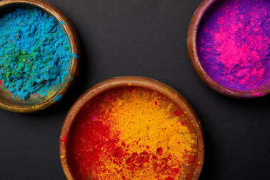 top view of colorful holi powder in paint on grey surface, Hindu spring festival