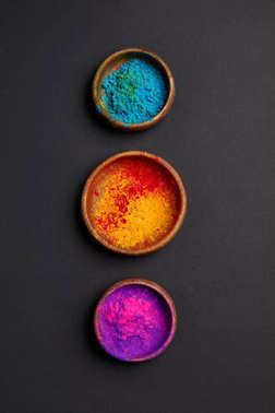 top view of colorful holi powder in bowls in row on grey surface