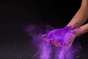 cropped view of female hands with purple holi powder, isolated on black