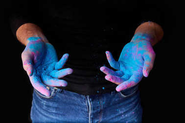 cropped view of man with blue traditional holi paint on hands, isolated on black