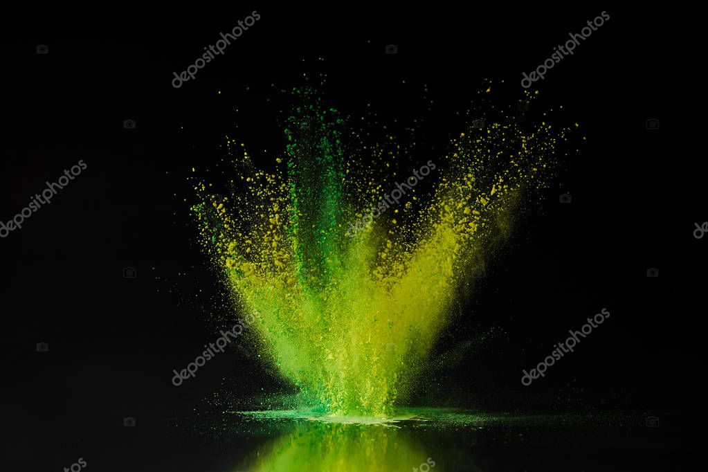 green and yellow holi powder explosion on black, traditional Indian festival of colours