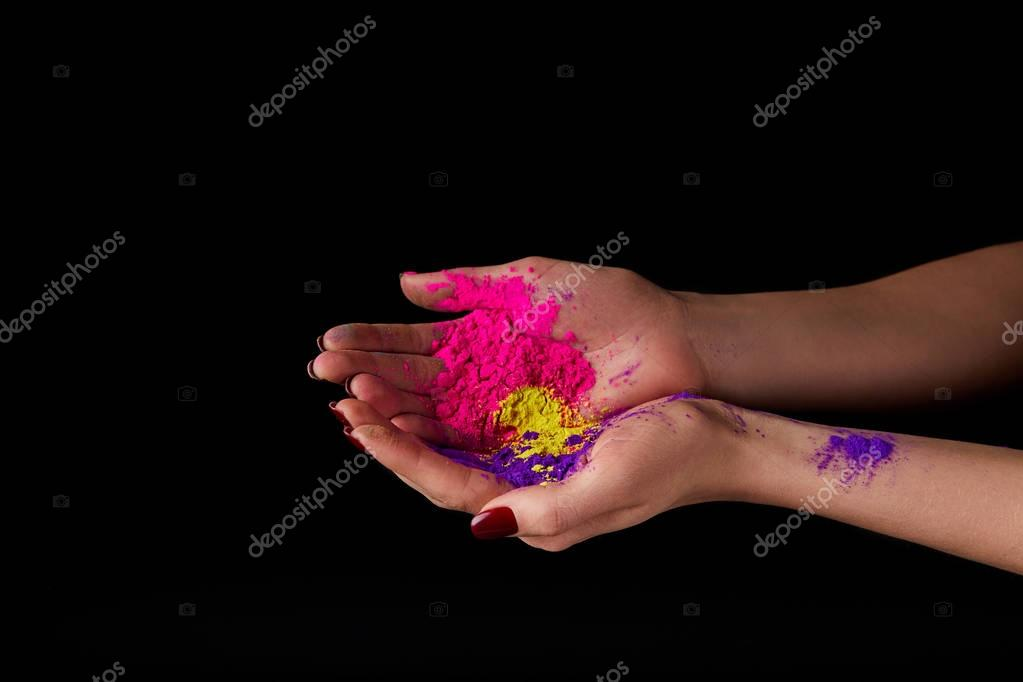 cropped view of woman holding powder for festival of colours, isolated on black