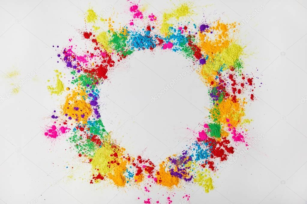 circle frame of multicolored traditional powder, isolated on white, festival of colours