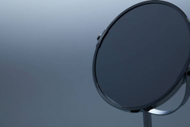 close-up shot of makeup mirror with stand on grey