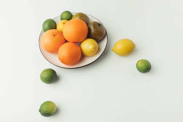 Citrus fruits on plate isolated on white background