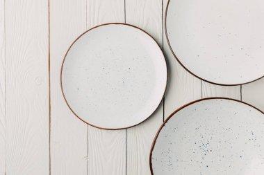 Ceramic glazed plates on white wooden background