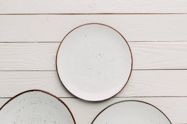 Empty ceramic plates on white wooden background