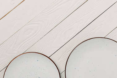 Empty glazed plates on white wooden background