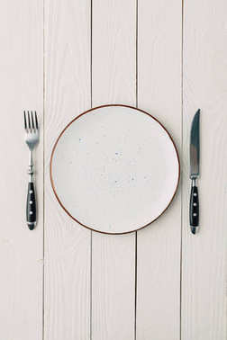 Top view of plate and cutlery on white wooden background