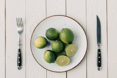 top view of green limes on plate and cutlery on white wooden background