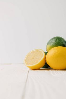 Green limes and lemons on white wooden background