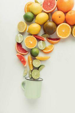 Assorted raw citruses and mug isolated on white background