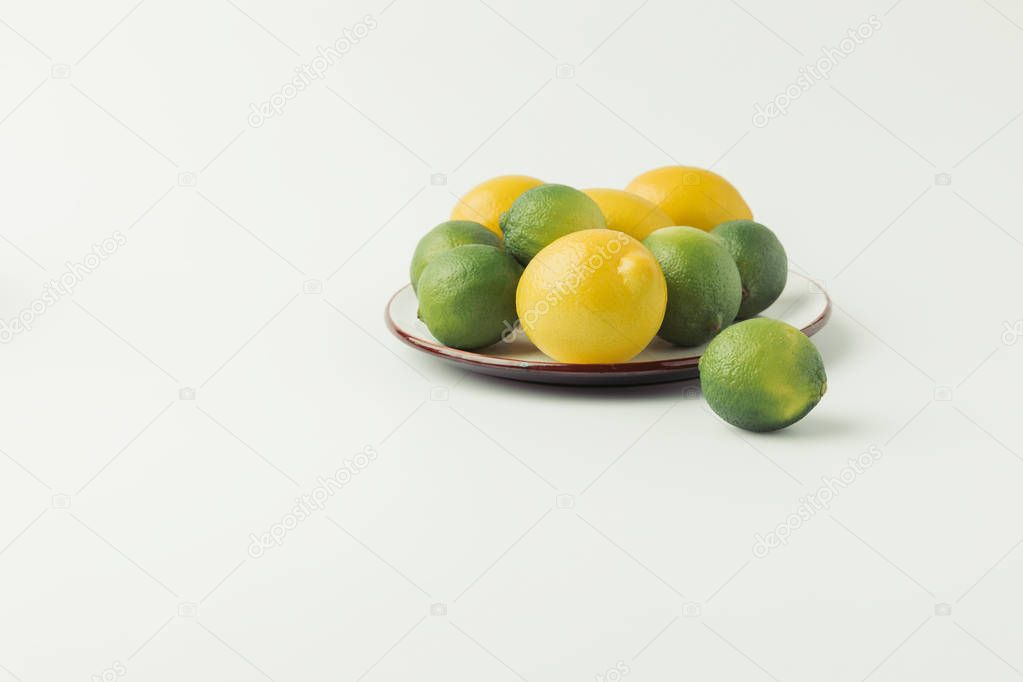 Citrus fruits on plate on white background