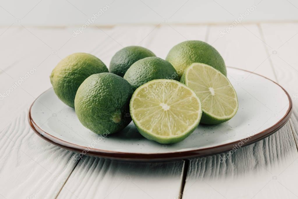 Green limes on plate on white wooden background