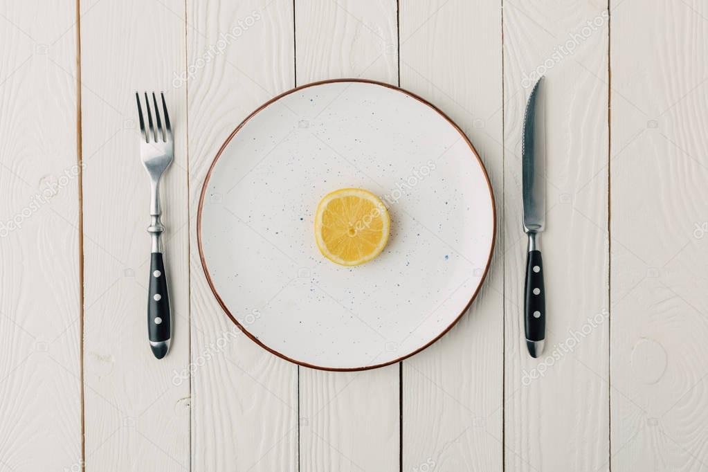 Half of juicy lemon on plate with cutlery on white wooden background