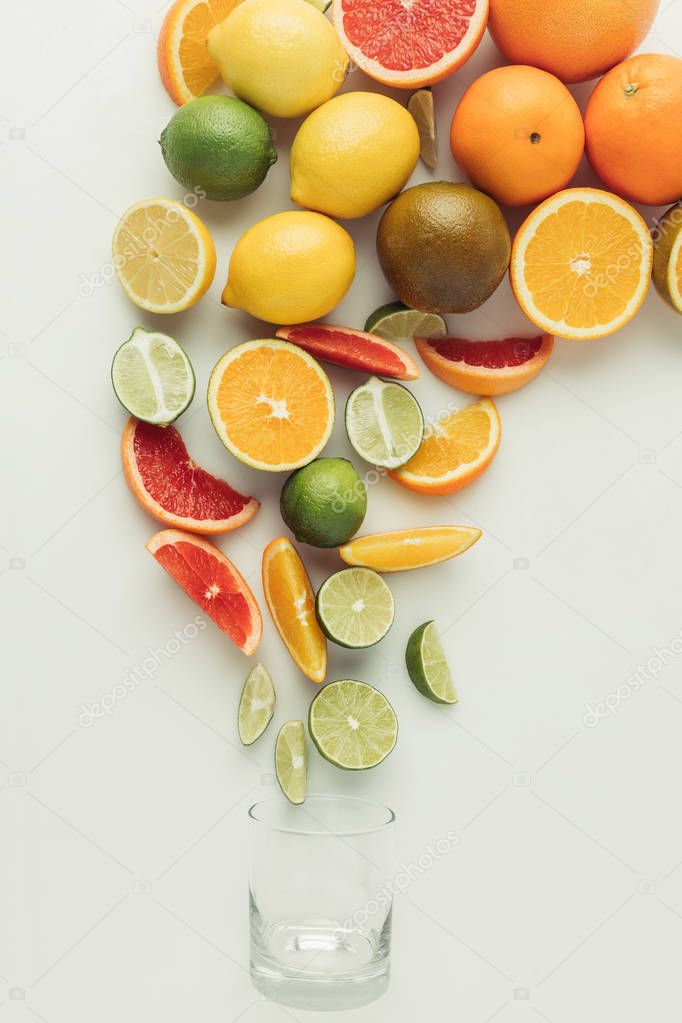 Heap of citrus fruits and glass isolated on white background