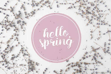 top view of HELLO SPRING lettering with round frame of lavender flowers on white tabletop