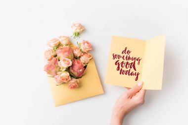 hand holding paper with DO SOMETHING GOOD TODAY inscription beside pink flowers in envelope isolated on white