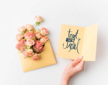 hand holding paper with TRUST YOUR SOUL sign beside pink flowers in envelope isolated on white