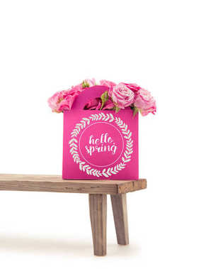 Close-up view of tender blooming rose flowers in pink paper bag with HELLO SPRING lettering on wooden bench isolated on white