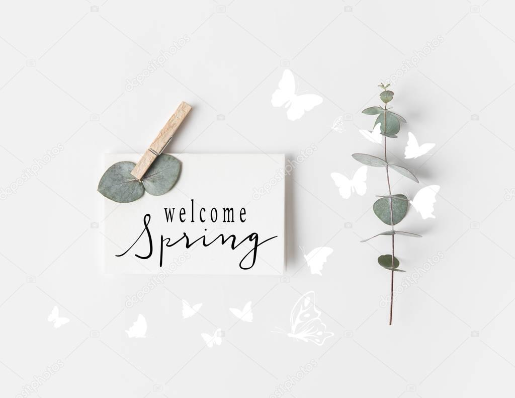 flat lay with eucalyptus and WELCOME SPRING sign on paper on white surface