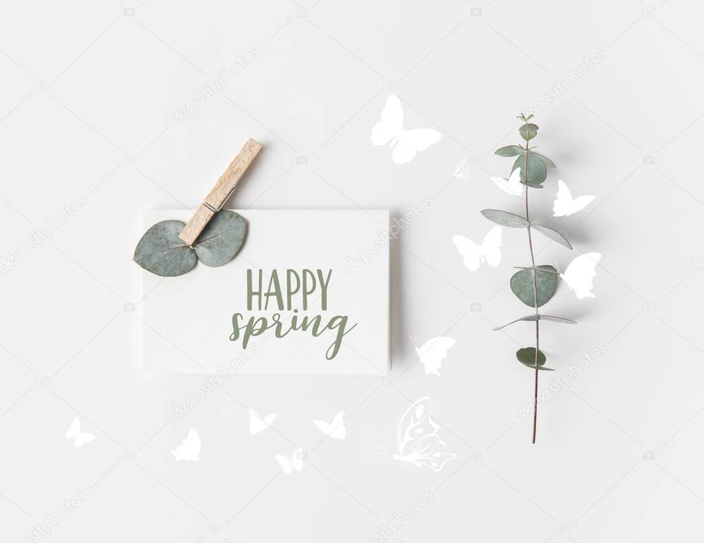 flat lay with eucalyptus and paper with HAPPY SPRING lettering on white surface