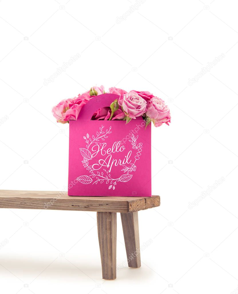 Close-up view of tender blooming rose flowers in pink paper bag with HELLO APRIL lettering on wooden bench isolated on white