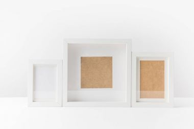close-up view of various empty white photo frames on white