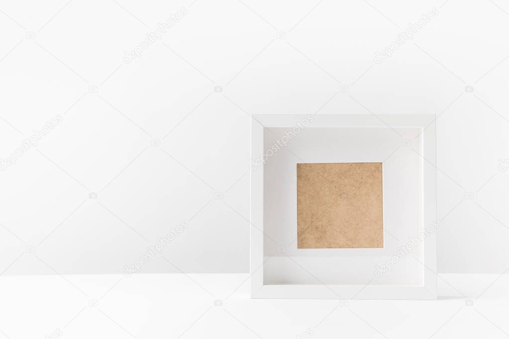 close-up view of empty white photo frame on white