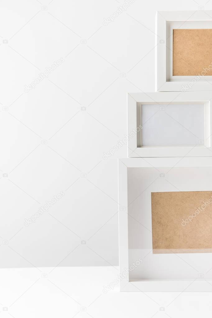 close-up view of empty white photo frames on white