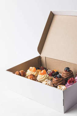 close up view of various types of cupcakes in cardboard box isolated on white