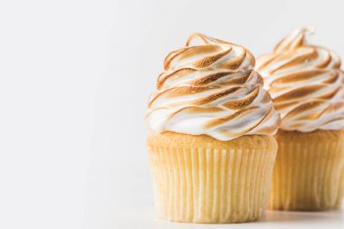 close up view of sweet cupcakes with meringue isolated on white