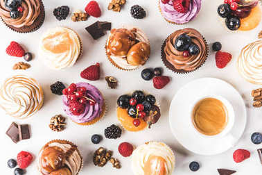 flat lay with cup of coffee, sweet cupcakes, berries, chocolate pieces and hazelnuts isolated on white