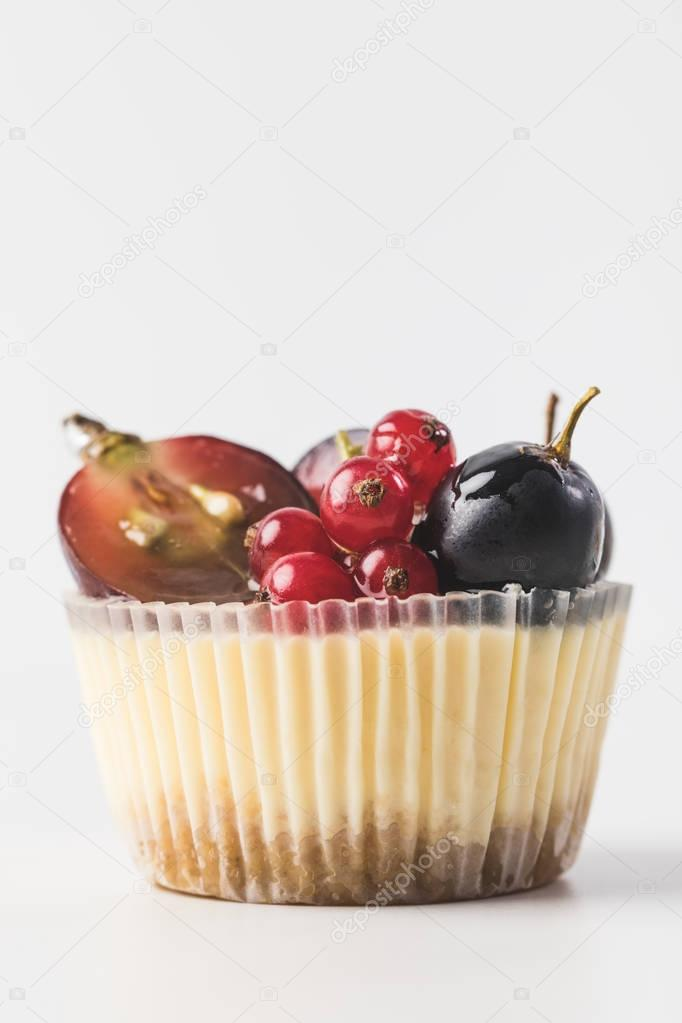 close up view of sweet cupcake with berries and fruits isolated on white