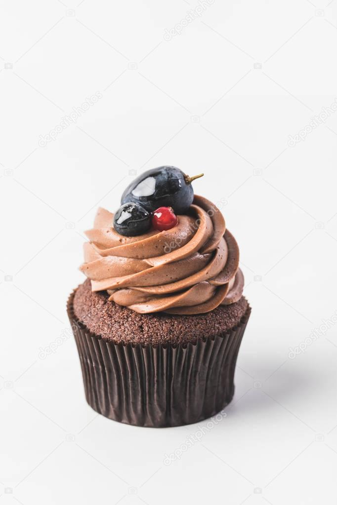 close up view of chocolate cupcake with cream, berries and plum isolated on white