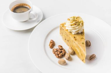 close up view of piece of cake with nuts and cup of coffee isolated on white