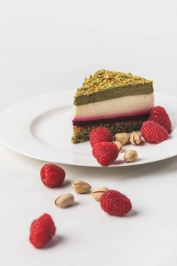 close up view of sweet cake with pistachios and raspberries on plate isolated on white